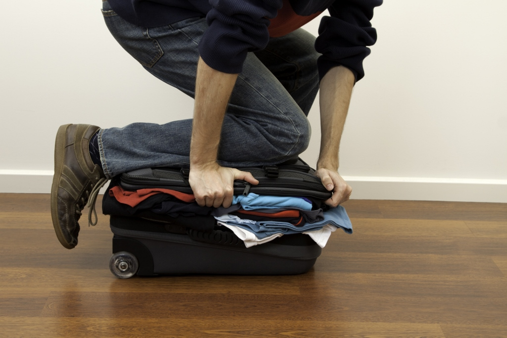 closing overflowing suitcase-shutterstock_61685038 (1024x683)