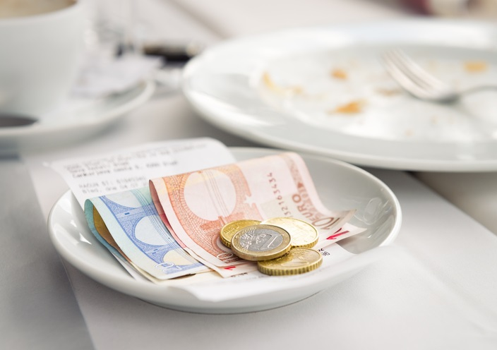 Euro notes and coins left on top of the bill at a European restaurant, as payment and a tip.