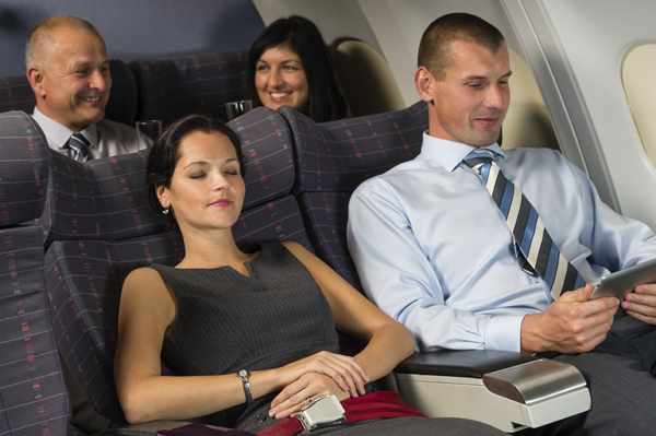 Business travelers relax on a plane