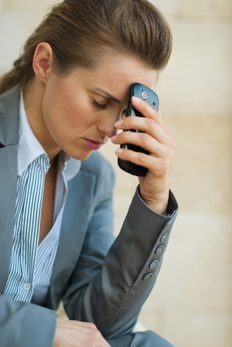Businesswoman worried with phone in hand