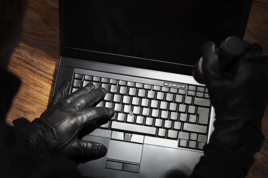 Man stealing data from a laptop