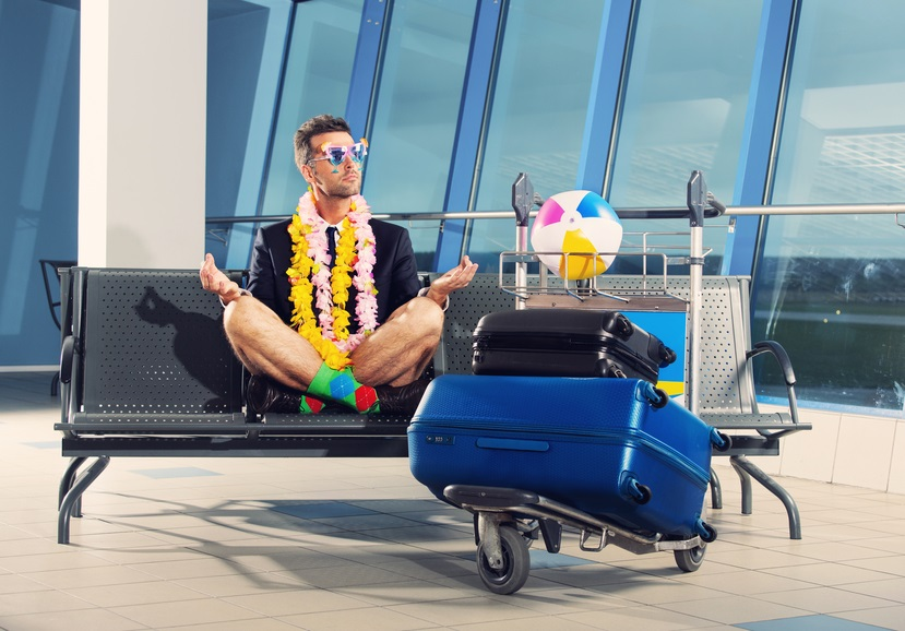 Portrait of businessman in a vacation mood, wearing beach shorts, garlands and sunglasses, sitting in yoga pose and waiting for the flight at the airport.