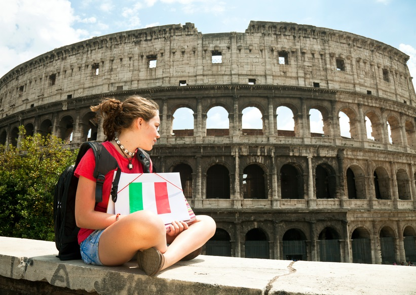 Teenager sitting in front of the Colisseum.