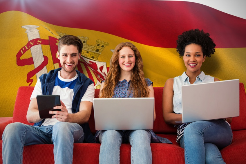 Young adults using electronic devices on couch  against digitally generated spanish national flag