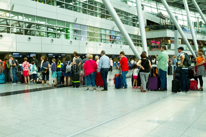 Düsseldorf, Germany - July 22, 2016: Capture of long queue of people and passengers at check-in of Finnair in hall of airport Düsseldorf in summer holiday season.