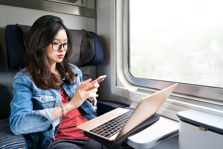 Cute Asian woman using smartphone and laptop on train